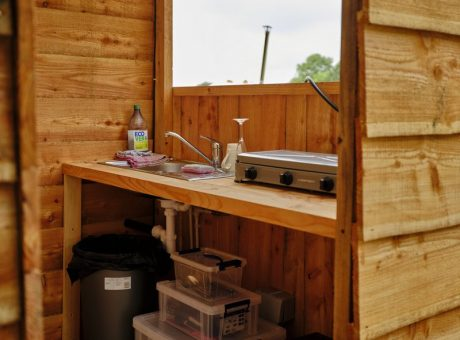 A wooden small cabin withe kitchen equipment in it, incising a sink, hob and bin