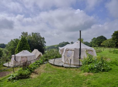 5 Glamping tents positions in green hill with blue skies and white fluffy clouds.